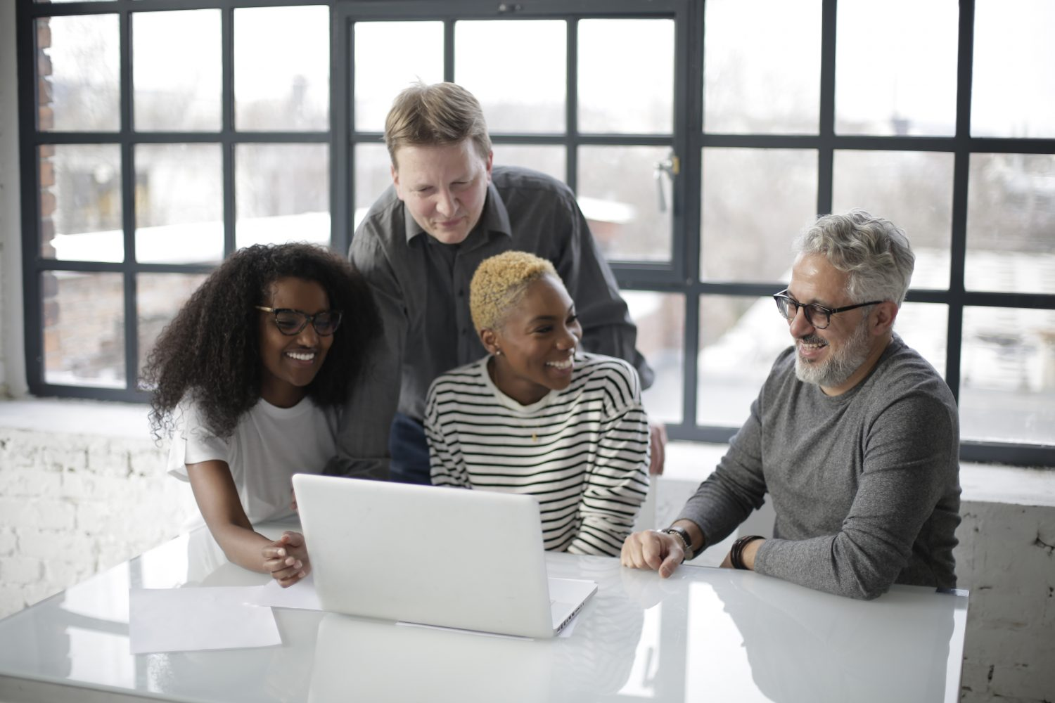 Four colleagues happily working together as a team. Photo by Andrea Piacquadio from Pexels