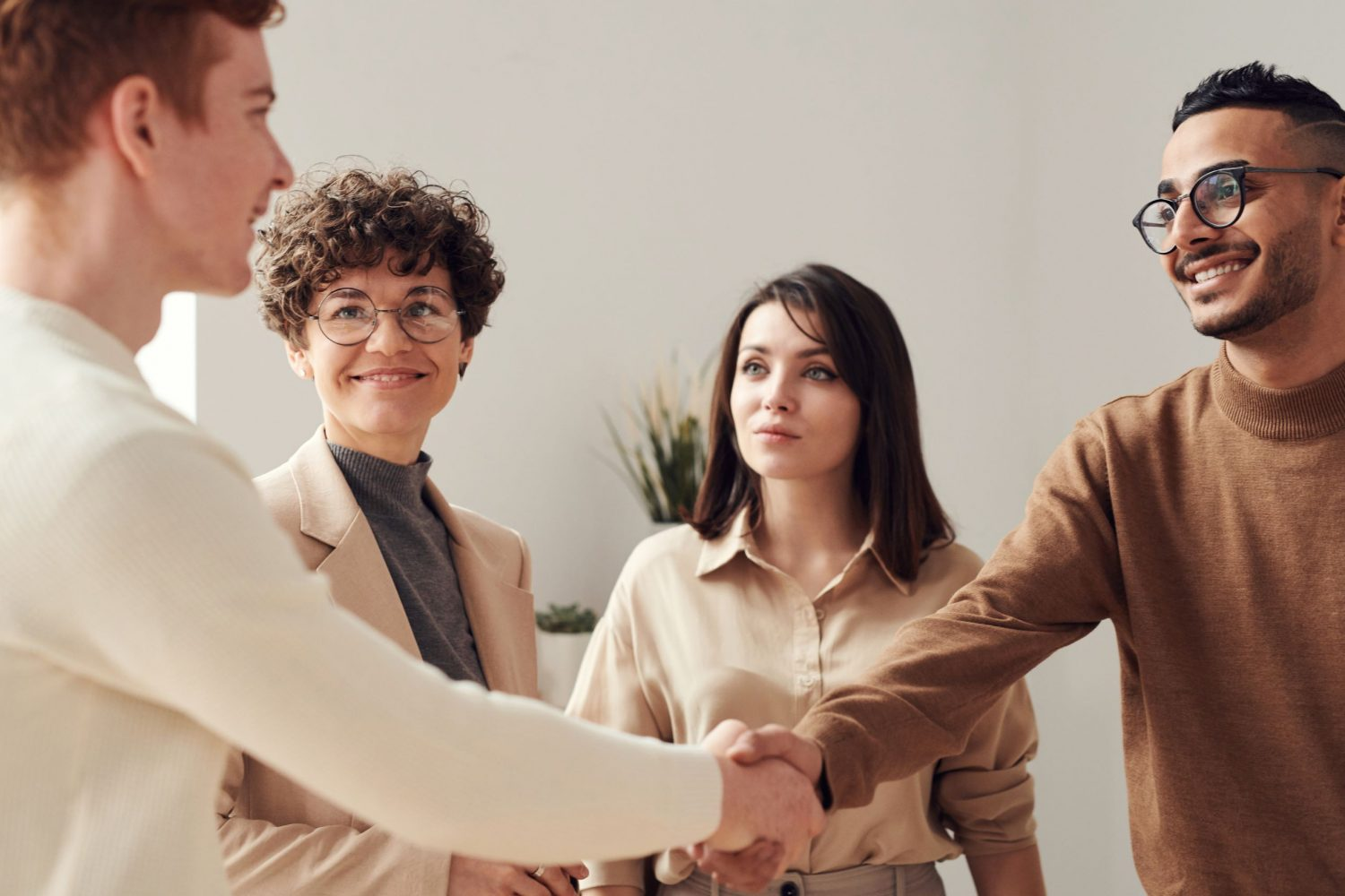 New colleagues shaking hands to welcome each other. Photo by Fauxels by Pexels